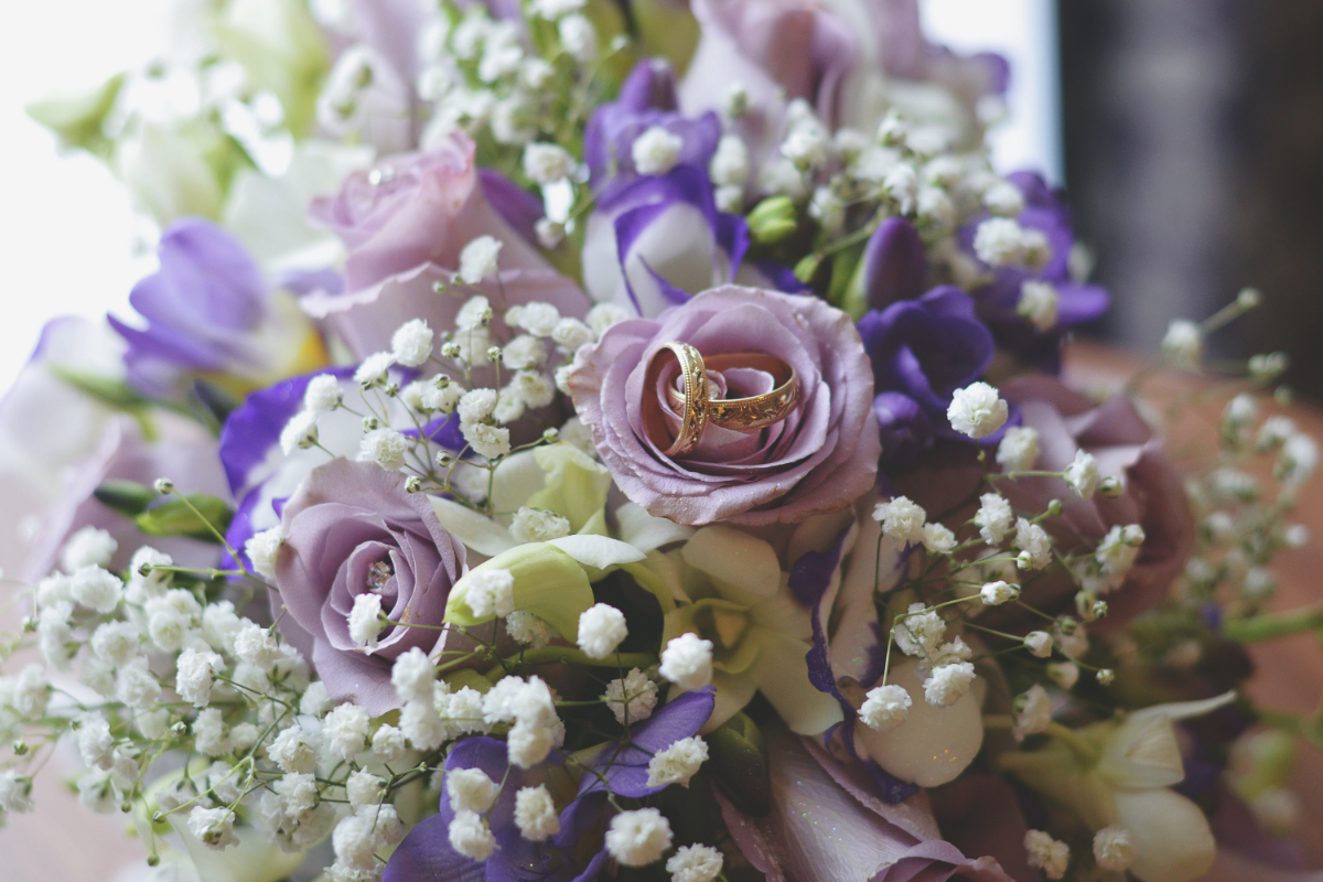 wedding rings placed on a lilac bunch of flowers
